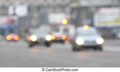 Defocused View of Cars Moving Through Street at Blurred City Lights Background