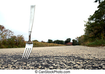 Fork in the Road - A fork stuck in the middle of the road.