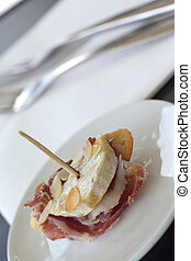 Skewer with ham and goar cheese on a plate