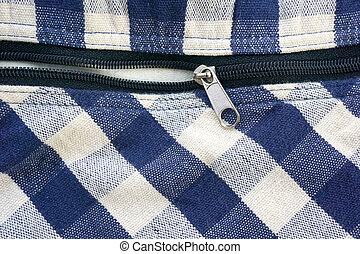 zipper on checked blue and white fabric background
