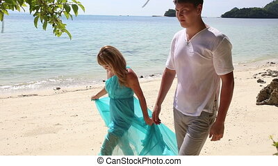 blonde girl in blue dress and  boyfriend walk along  beach