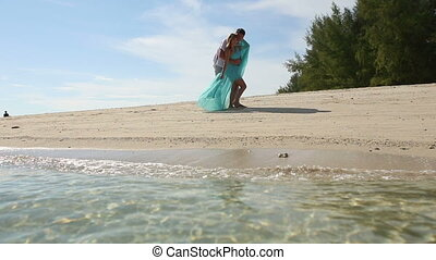 handsome guy embraces and kisses blonde girl on sand beach of island