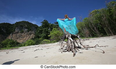 blonde girl stands on root top waving blue dress