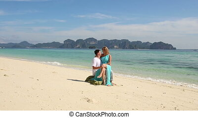guy sits on stone  with blonde girl they kiss talk on beach near sea