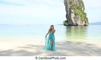 blonde girl stand on beach against tranquil transparent...