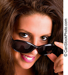 Smiling Young Brunette Looking over Sunglasses - Close-up of...