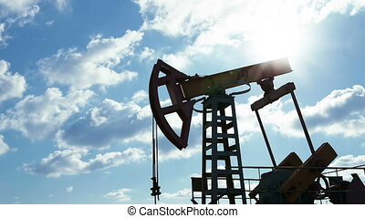 Oil pump - Oil pump machine working over bright sky