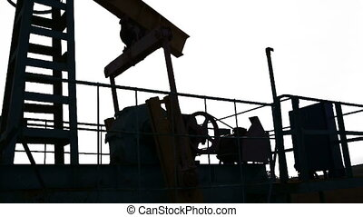 Oil pump. - Oil pump machine working over bright sky.