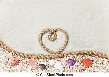 Heart shape rope on sand background