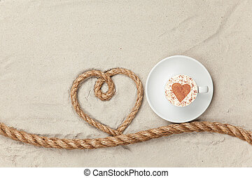 Cup of coffee near heart shape rope on sand background