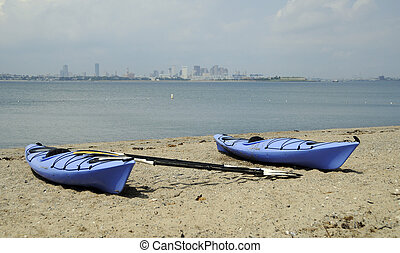 Kayaking Boston Harbor - Two Blue kayaks along shore of...