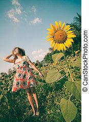 Woman happy in sunflower flower field.