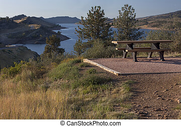 picnic table on shore of mountain reservoir - picnic table...