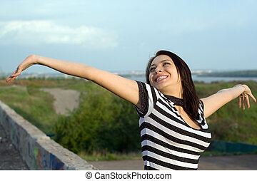 Happy young woman with arms raised outdoors