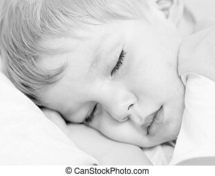 Sleep - Little boy sleep on white bed. High key