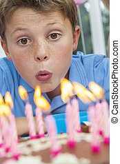 Boy Child Blowing Out Birthday Cake Candles - Happy male boy...