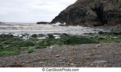 Waves rolling in along the shore of North Wales, UK - White...