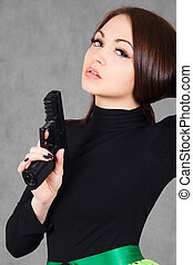 Portrait of a young attractive woman with a gun over grey...