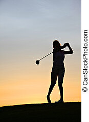 Golf swing - Lady golfer swinging her driver at sunrise.