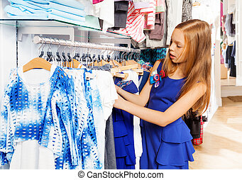 Blond girl in blue dress choosing clothes at store