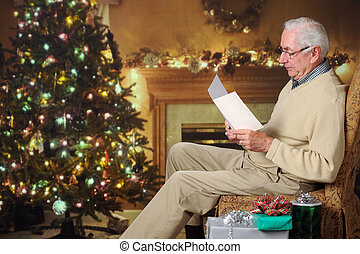 Reading a Card - A senior man reading a card in a living...