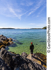 Woman Stands on Rocks to Admire the Ocean