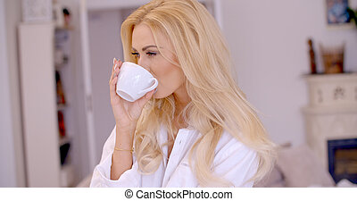 Young woman smiling in pleasure enjoying coffee - Young...