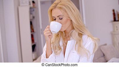 Young woman smiling in pleasure enjoying coffee