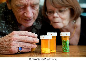 Man and woman looking at prescription medications - Man and...