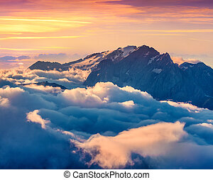 Colorful summer sunrise on the foggy Val di Fassa valley...