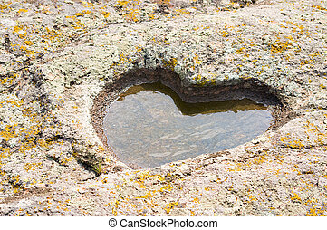 stone granite heart with puddle and moss