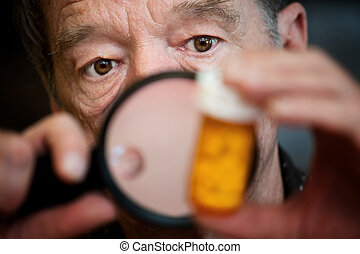 Man examining instructions on medicine bottle - Man closely...