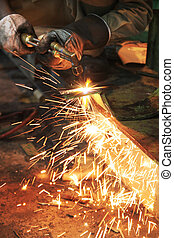 Industrial worker use acetylene torch cutting flat steel