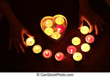 Candle light with woman hand hold metal heart shape