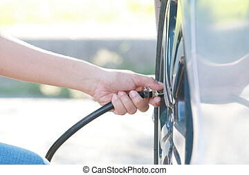 woman inflating car tire. - close up,woman checking pressure...