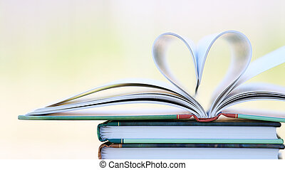Book page in heart shape with green garden background