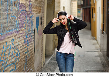 Woman in urban background listening to music with headphones...