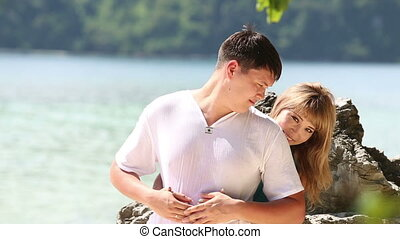blonde asian girl sitting on rock embraces guy - pretty...
