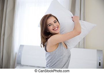 Portrait of a smiling woman holding pillow at home
