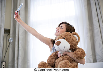 Smiling woman taking a selfie portrait with teddy bear