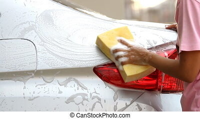 Woman Washing a silver car with a yellow sponge and soap...