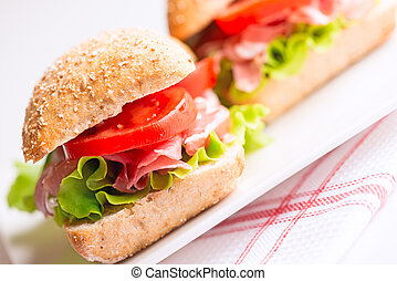 Prosciutto sandwiches with tomato and arugula on plate