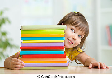 Cute kid girl preschooler with books at home