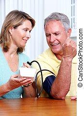 Blood pressure measuring. - Senior woman and man measuring...
