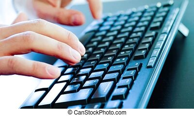man typing on a pc keyboard - Close-up of a young man typing...
