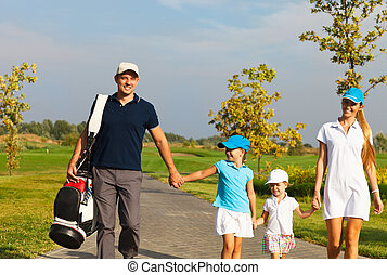 Family of golf players walking at the course