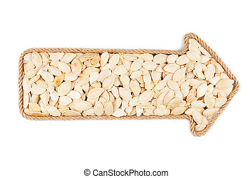 Arrow made of rope with pumpkin seeds, on a white background...