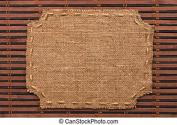 Frame of burlap, lies on a background of bamboo mat, with...