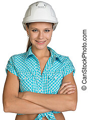 Pretty girl in shirt and white helmet standing with crossed...