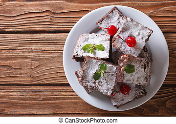 brownies with mint and cherries on a plate. horizontal top view